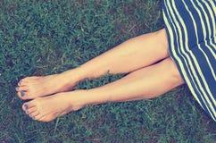 Fille dans la jupe se trouvant sur l'herbe verte Le concept du repos, de la tranquilité et de la relaxation Photographie stock libre de droits