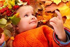 Fille dans la lame orange d'automne et la baie rouge. photo stock