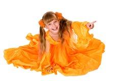 Fille dans la longue robe orange avec l'indication par les doigts. Image libre de droits