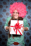 Fille dans la perruque rose avec le cadeau Photographie stock