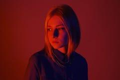 Fille dans la pièce allumée par rouge Concept de studio Photographie stock