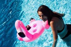 Fille dans la piscine avec un flotteur de flamant photo libre de droits
