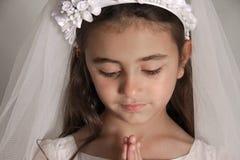 Fille dans la prière de robe de communion sainte Photo libre de droits