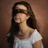 Fille dans la robe blanche avec des cheveux sur son visage sur le fond brun Image libre de droits