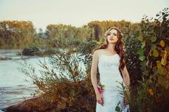 Fille dans la robe blanche près de la rivière Photo stock