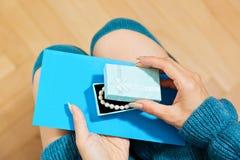 Fille dans la robe bleue déballant un cadeau Photo libre de droits
