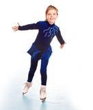 Fille dans la robe bleue de sport sur des patins. Photos stock