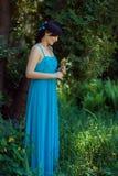 Fille dans la robe bleue se tenant près d'un arbre Image libre de droits