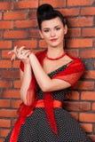 Fille dans la robe de vintage près du mur de briques Photographie stock libre de droits