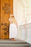 Fille dans la robe et l'écharpe blanches sur le fond des portes en bois travaillées et des colonnes blanches Image stock