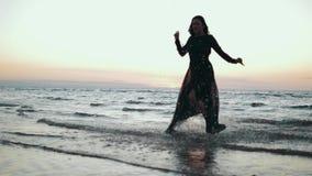 Fille dans la robe foncée fonctionnant sur l'eau sur la côte Photoshoot Éclaboussure modèle Mer banque de vidéos