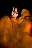 Fille dans la robe orange du tissu de vol Images stock