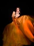 Fille dans la robe orange du tissu de vol Photographie stock libre de droits