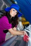 Fille dans la robe pourprée et le chapeau bleu photos stock