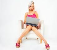Fille dans la robe rose avec l'ordinateur portatif Photos stock