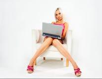 Fille dans la robe rose avec l'ordinateur portatif Images libres de droits