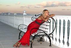 Fille dans la robe rouge de soirée se reposant sur un banc Image libre de droits