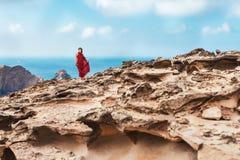 Fille dans la robe rouge parmi des roches et des falaises le long de la côte d'Algarve Photographie stock libre de droits