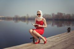 Fille dans la robe rouge se reposant sur une jetée Photographie stock libre de droits