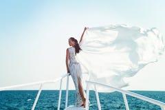 Fille dans la robe sur le ciel bleu à l'océan Image stock