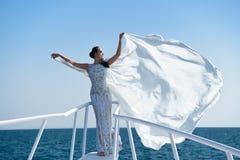 Fille dans la robe sur le ciel bleu en mer Photographie stock