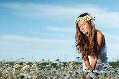 Fille dans la robe sur le gisement de fleurs de marguerite Photographie stock libre de droits