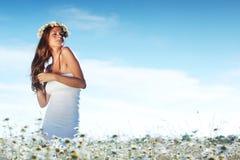 Fille dans la robe sur le gisement de fleurs de marguerite Photographie stock