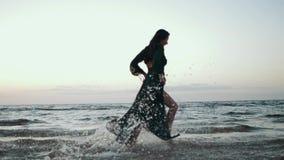 Fille dans la robe vert-foncé fonctionnant sur l'eau sur la côte Photoshoot Éclaboussure modèle banque de vidéos