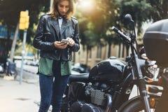 Fille dans la veste en cuir tenant le téléphone intelligent sur la moto de fond dans la ville atmosphérique de fusée du soleil, h photographie stock libre de droits