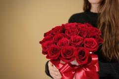 Fille dans la veste noire tenant le bouquet riche disponible de cadeau du rouge 21 Photographie stock libre de droits