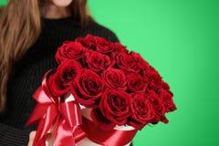 Fille dans la veste noire tenant le bouquet riche disponible de cadeau du rouge 21 Photo stock