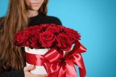 Fille dans la veste noire tenant le bouquet riche disponible de cadeau du rouge 21 Images stock