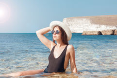 Fille dans le bikini, les verres et le chapeau en eau de mer claire Photographie stock libre de droits