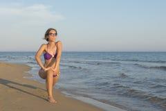 Fille dans le bikini s'étendant et s'exerçant à la plage Photos libres de droits