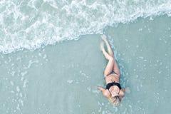 Fille dans le bikini se trouvant sur la plage Photos libres de droits