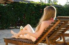 Fille dans le bikini sur la chaise longue avec la crème glacée à disposition Image libre de droits