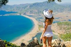 Fille dans le blanc sur une haute falaise Photographie stock libre de droits