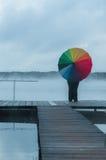 Fille dans le brouillard sur le pilier avec un parapluie d'arc-en-ciel examinant la distance, vue du dos Photographie stock