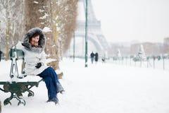 Fille dans le capot de fourrure se reposant sur un banc près d'Eiffel à Image stock