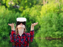 Fille dans le casque de la réalité virtuelle dans la perspective de la nature Mains vers le haut Photo stock