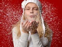 Fille dans le chapeau blanc soufflant sur la neige sur ses mains sur le rouge photographie stock libre de droits