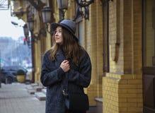 Fille dans le chapeau de feutre, marchant autour des rues de ville, jour nuageux, extérieur Photographie stock