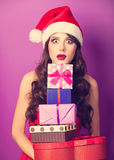 Fille dans le chapeau de Noël avec des cadeaux images stock
