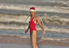 Fille dans le chapeau de Noël avec le cercle de danse polynésienne sur la plage Photographie stock libre de droits