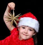 Fille dans le chapeau de Noël jouant avec l'étoile d'or Photographie stock libre de droits