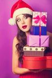 Fille dans le chapeau de Noël avec des cadeaux Image stock