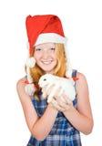 Fille dans le chapeau de Santa avec le lapin d'animal familier Image libre de droits
