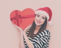 Fille dans le chapeau de Santa Claus avec le boîte-cadeau Photo stock