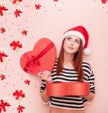 Fille dans le chapeau de Santa Claus avec le boîte-cadeau Image stock