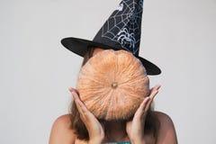 Fille dans le chapeau de sorcière de Halloween avec le potiron Images libres de droits